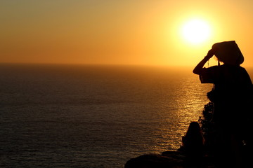 Sunset silhouettes with strange chinese hat during amazing golden sunset in Ibiza