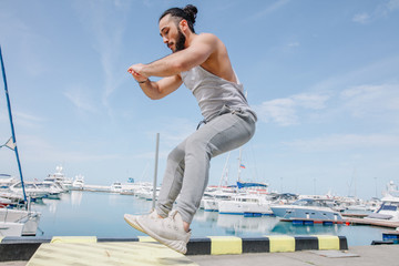 Extreme Jump Squats fitness training. Crossfit Athlete caucasian man doing High jump squat exercise workout on makeshift box at the marina summer pier