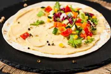 Tortilla with vegetables and hummus with chickpeas.