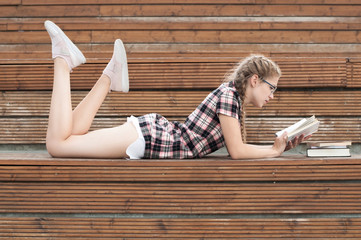 cute nerd girl in a short dress lies with a book on wooden steps