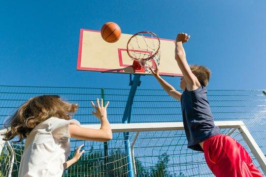 Streetball basketball game with two players, teenagers girl and boy, morning on basketball court.