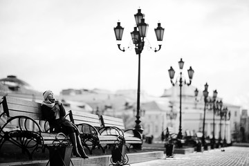 woman on a bench in a winter city