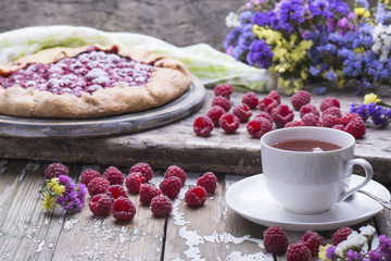 The cup of fresh tea with homemade biscuit of fresh natural raspberries and flowers on a wooden table.