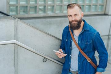 Casual bearded man walking up urban stairs