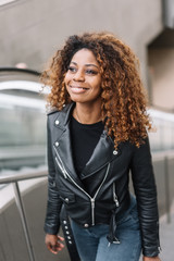 Young black smiling woman going up escalator