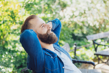 Young bearded man sitting daydreaming