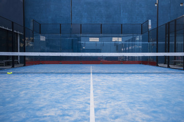 Paddle tennis court, net, racket, balls.