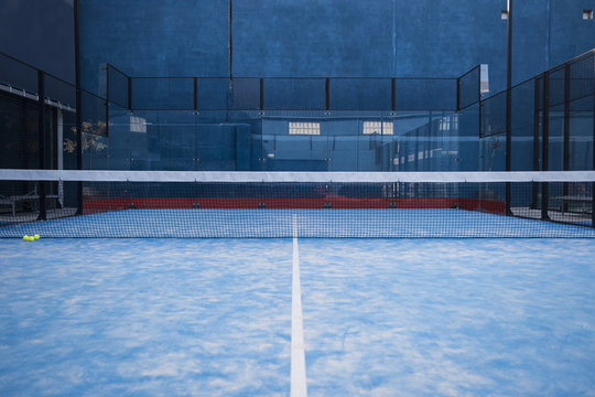 Paddle tennis court, net, racket, balls.