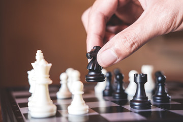 Hand of confident businessman use horse chess piece black playing chess game to development analysis new strategy plan, business strategy for win and success