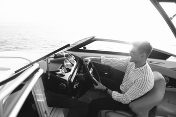 Aspirational successful mid-aged caucasian businessman sitting behaind the wheel of speed motorboat, driving at open sea, enjoying with speed.
