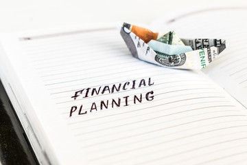 Open notepad with the handwriting text FINANCIAL PLANNING and the boat from the us dollar banknote.  Business, banking, finance and investment concept