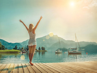 Happiness blonde woman stay on the wooden pier near the mountain