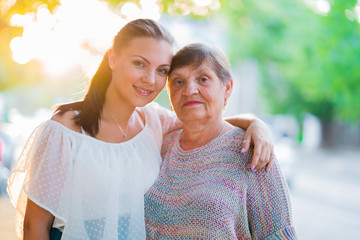 Beautiful portrait of grandmother and her granddaughter standing outdoor on summer street. Golden hour, sun flares. Girl embracing granny with love. Family concept