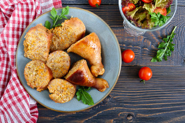 Tasty stuffed chicken legs with salad of fresh vegetables on a wooden background. Top view. Rolls with chicken and vegetables