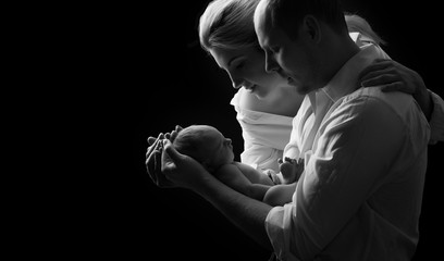 Newborn baby lying on the hands of parents on a black background