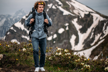 handsome adventurous man travelling on the mountaines. full length photo.blurred high mountaines on the background of the photo. hiking abd backpacking concept