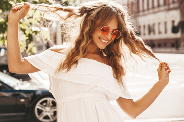 Portrait of beautiful cute blond teenager model with no makeup in summer hipster white dress clothes posing on the street background in sunglasses