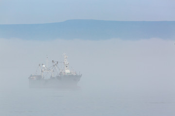 Fishing boat in thick fog on the background of mountains