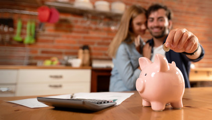 Happy couple inserting coin in piggybank