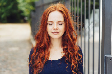 Serene young woman standing with closed eyes