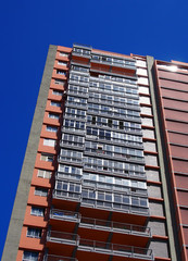 vertical angled view of a tall concrete apartment block with balconies against a blue sky