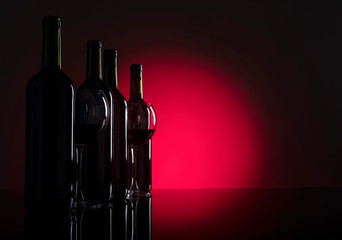 Glasses and bottles of red wine.