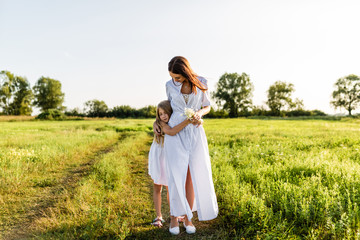 beautiful mother and daughter embracing in green meadow on sunset