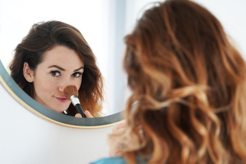 young woman powdering her nose with make-up brush seen in bathroom mirror, selective focus