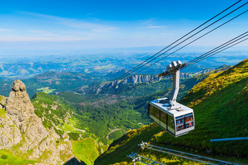 cable car on the ropes, going to Mount Kasprowy Wierch, Poland. Beautiful view of the valley Wall mural