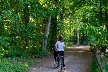 Jovem montada em bicicleta numa estrada de terra no meio de uma floresta