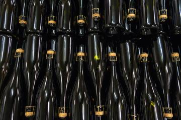 Bottiglie in vetro scuro con tappo in sughero e gabbietta in posizione orizzontale in una cantina vinicola