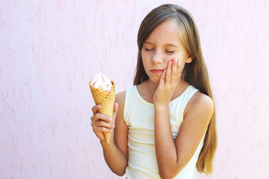 Girl has a toothache from cold ice cream.