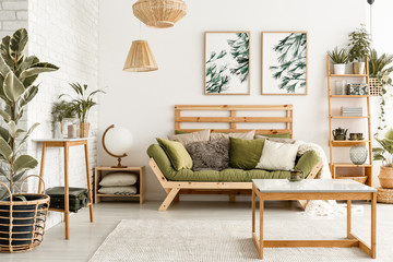 Wooden table on carpet in front of green couch in living room interior with plants and posters. Real photo