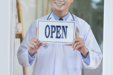 Unrecognizable male in medical apparel smiling and holding open sign while standing behind glass in office