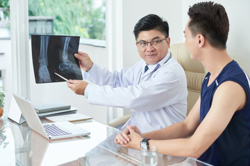 Adult Asian man in medical apparel demonstrating X-ray picture of legs to young guy while sitting at table in doctor's office