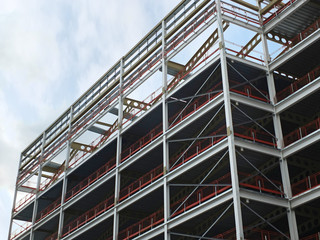 angled view of a large building development under construction with steel framework and girders supporting the metal floors with blue sky and clouds