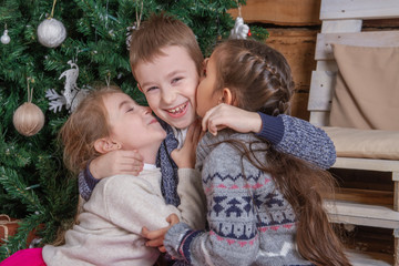 Teen girls kissing brother under Christmas tree, everybody laughing