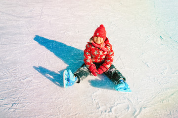 happy little girl learning to skate in winter