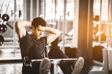 Fit handsome caucasian man sit up on machine in sportswear. Young man sit up exercise to strengthen their core abdominal muscles at fitness training in gym. Healthy, Sports, Lifestyle, Fitness concept