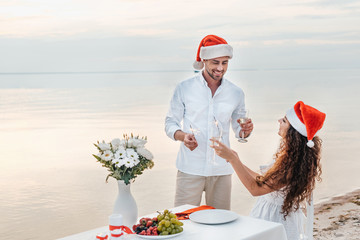romantic couple in santa hats celebrating new year with champagne glasses and sparklers on beach