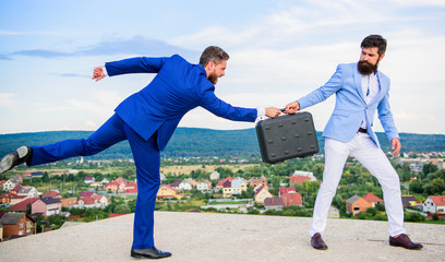 Rascal racketeer extortionist cheating handover. Men suits handover briefcase. Business deal landscape background. Businessman takes away briefcase from business partner. Fraud and extortion concept