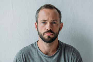portrait of unhappy bearded man looking at camera on grey