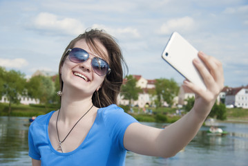 Beautiful woman, instagram. woman taking a selfie with smart phone outdoors in the city on sunny summer day. Closeup shot.