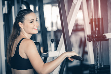 Fit beautiful young woman exercise workout on machine in gym. Glad smiling girl is enjoy with her training process. Concept of fitness, Healthy, Sport, Lifestyle