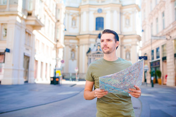Man tourist with a city map in Europe street. Caucasian boy looking with map of European city.