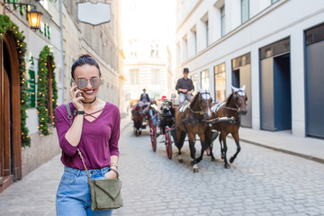 Woman talk by her smartphone in city. Young attractive tourist outdoors in italian city