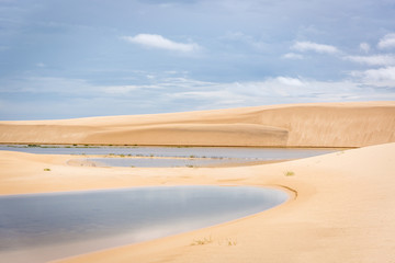 The colorful vast desert landscape of tall, white sand dunes and seasonal rainwater lagoons in a cloudy day at the Lençóis Maranhenses National Park, Brasil