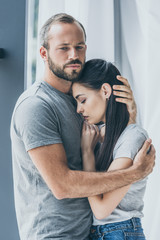 upset bearded man hugging and supporting depressed young woman