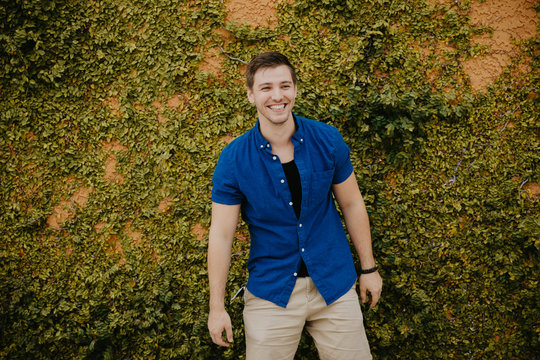 Attractive Male Model in Blue Collared Shirt in front of Orange Textured Vine Wall