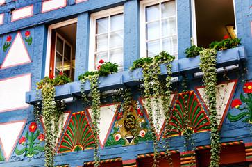 Ein altes Fachwerkhaus mit Blumenschmuck und farbigen Ornamenten in Alsfeld